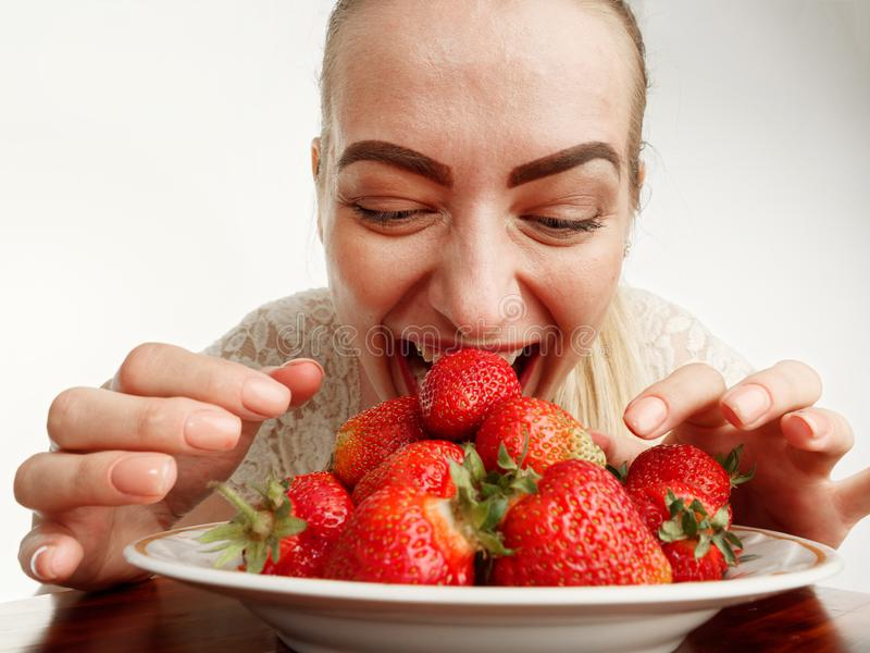 Girl eagerly eating strawberries on white background. 5 stock photos