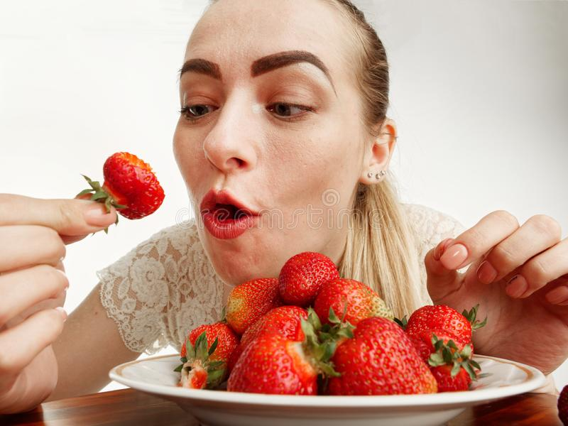 Girl eagerly eating strawberries on white background. 5 royalty free stock image