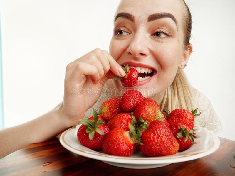 Girl eagerly eating strawberries on white background. 5 stock photography