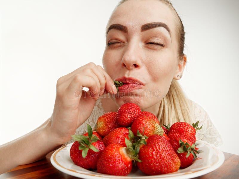Girl eagerly eating strawberries on white background. 5 stock photo