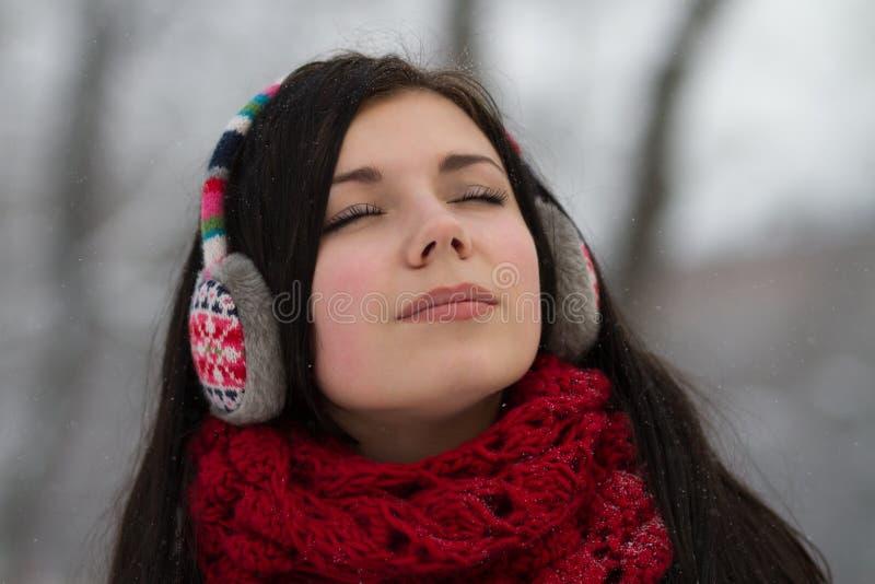 Girl in earplugs outdoors in winter royalty free stock image