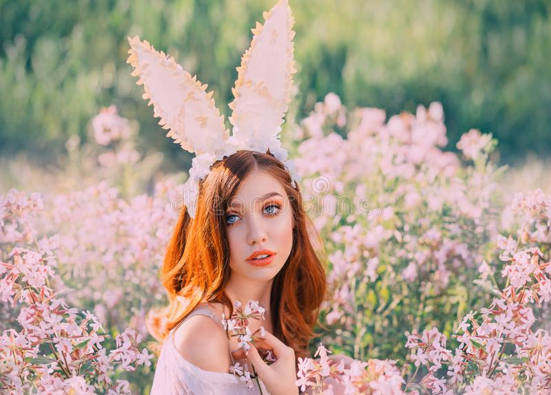 Girl easter bunny with creative ears on the hoop. Portrait of a young, red-haired woman with big beautiful eyes and lips. Rabbit sits in a flowery pink field stock photo