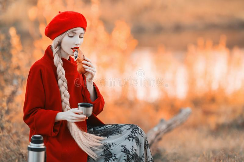 Girl eat bun and drink coffee. Blonde woman with long hair in red coat on autumn background. Girl drink tea from thermos cup on. Background of forest. Hot tea royalty free stock photography