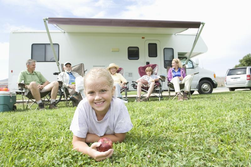 Girl Eating Apple With Family Sitting Outside RV Home royalty free stock image