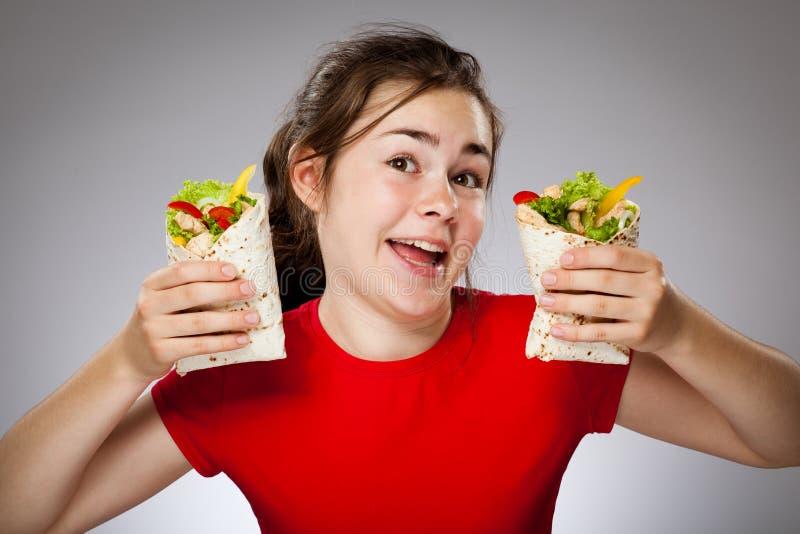 Girl eating big sandwich. Happy young girl eating big sandwich stock images
