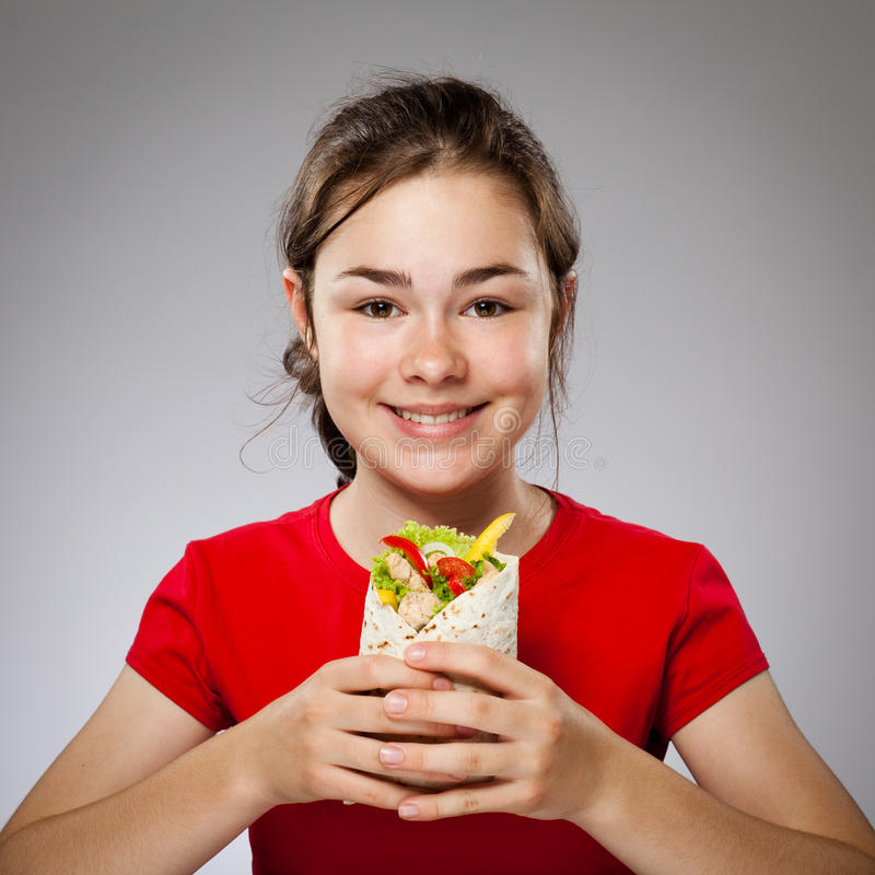 Girl eating big sandwich - focus on front. Happy young girl eating big sandwich royalty free stock photography