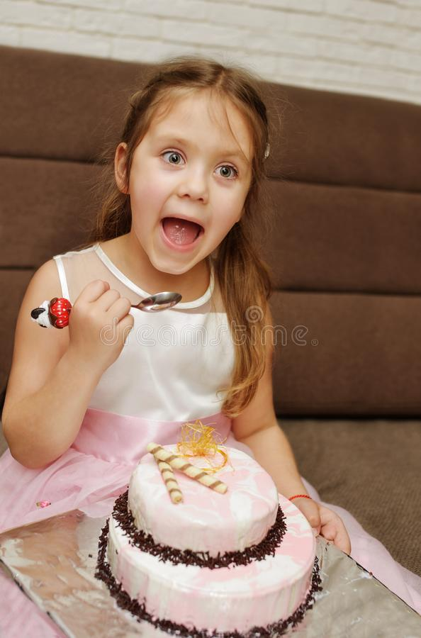 Girl eating birthday cake. Funny kid girl eating birthday cake with open mouth royalty free stock image