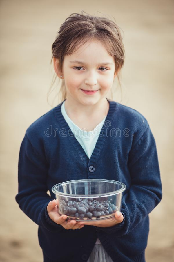 The girl eating blueberries from a glass bowl royalty free stock photos