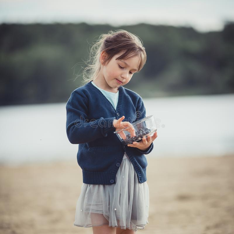 The girl eating blueberries from a glass bowl stock photos