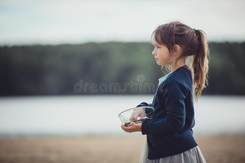 The girl eating blueberries from a glass bowl royalty free stock image