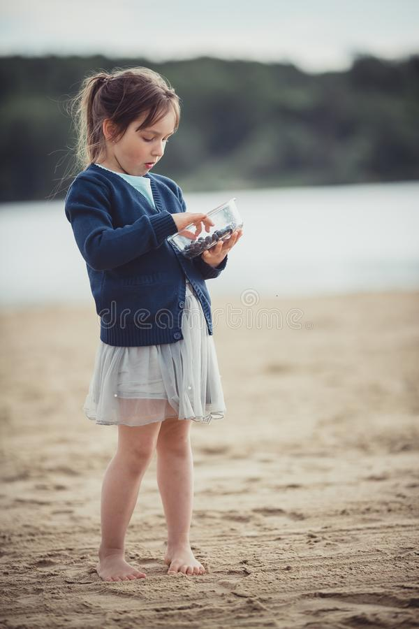 The girl eating blueberries from a glass bowl royalty free stock photography