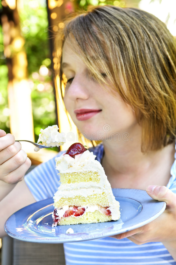 Girl eating a cake royalty free stock image