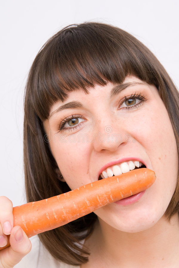 Girl eating carrot royalty free stock photography