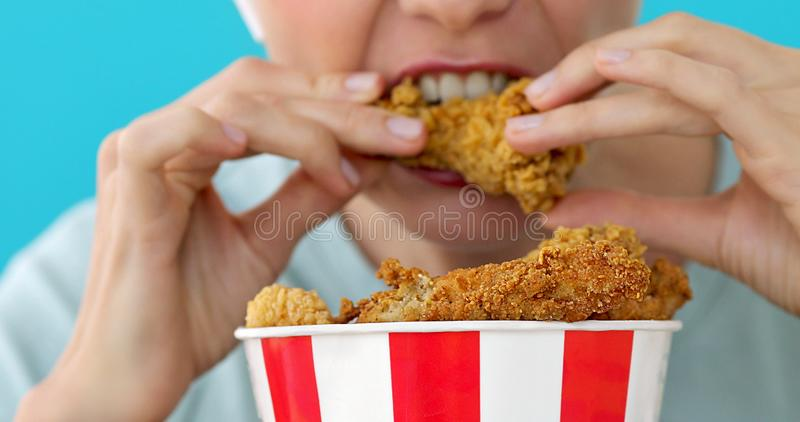 Girl eating chicken wings. High calorie food and health risks, cholesterol blue background royalty free stock photography