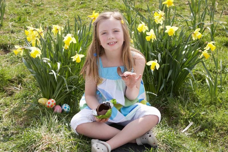 Download Girl Eating Chocolate Egg On Easter Egg Hunt Stock Photo - Image: 16143038