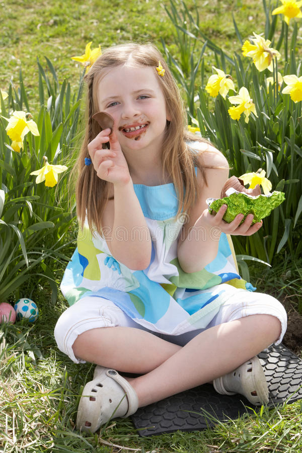 Girl Eating Chocolate Egg On Easter Egg Hunt Royalty Free Stock Images