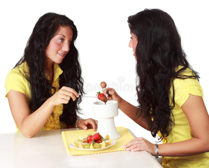 Girl eating chocolate fondue stock images