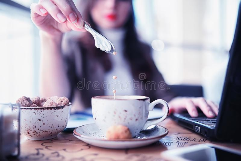 Girl eating coffee cakes. And drinking coffeer royalty free stock images