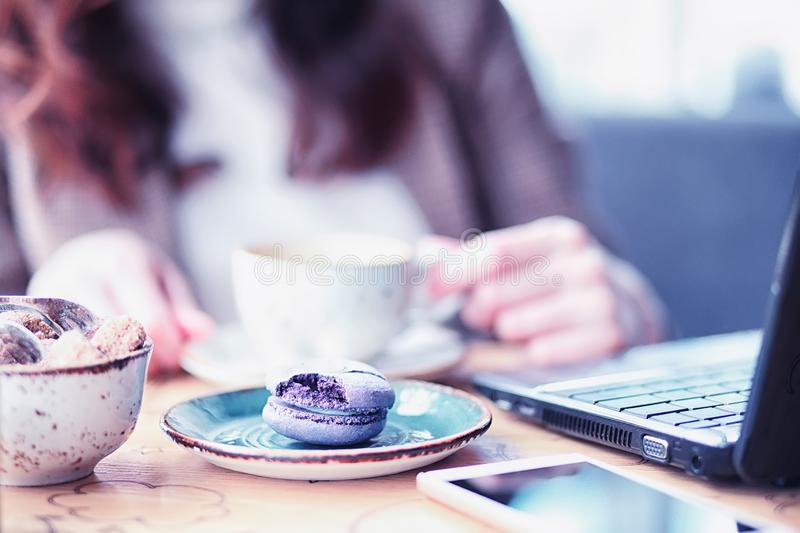 Girl eating coffee cakes. And drinking coffeer royalty free stock photography