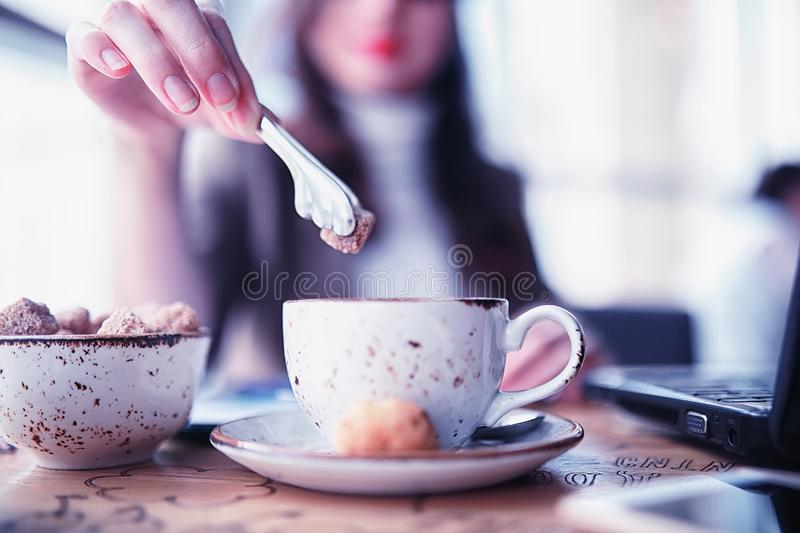 Girl eating coffee cakes. And drinking coffeer stock photography