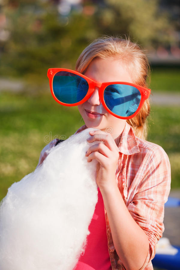 Download Girl eating cotton candy stock photo. Image of glasses - 25245868