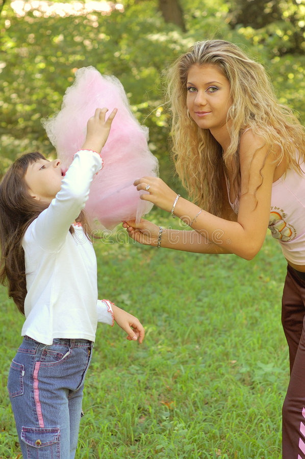Girl eating cotton candy royalty free stock photo