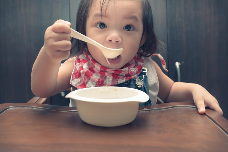Girl eating. Cute funny girl eating at a wood table royalty free stock photos