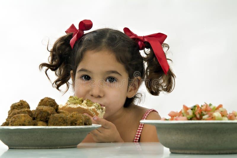 Girl eating falafel. Young happy Israeli girl eating Falafel in pita bread stock photos