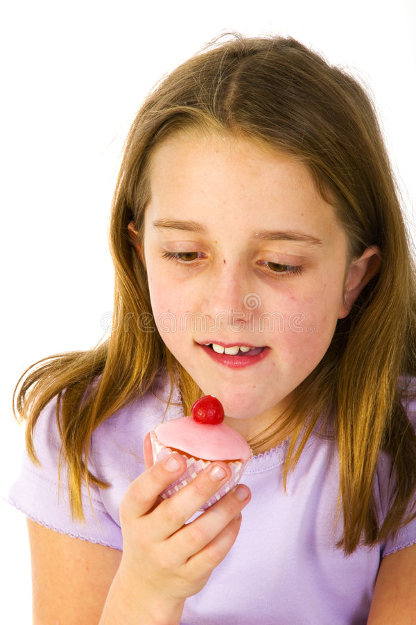Girl is eating fancy cakes. Cute girl is eating sweet fancy cakes royalty free stock photo