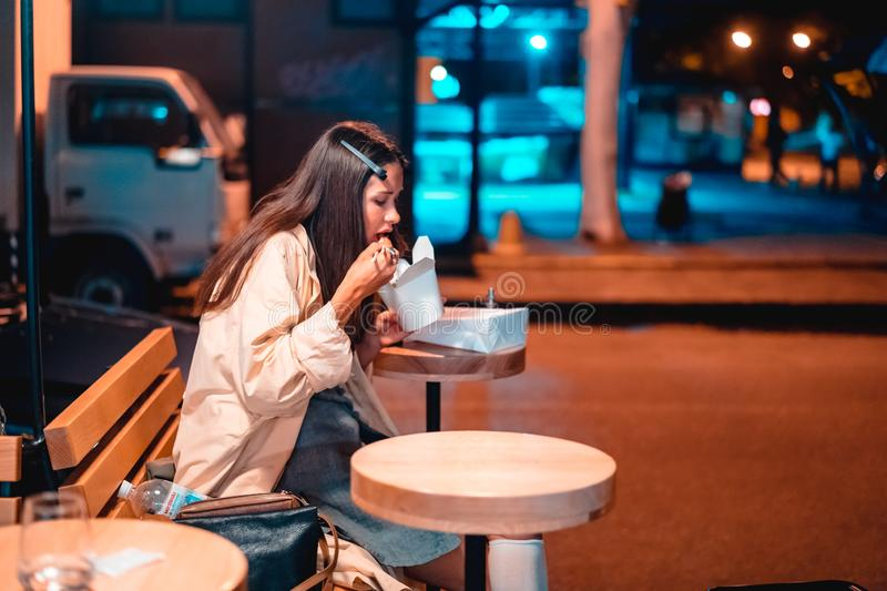 The girl is eating fast food, on the street of the night city. Girl eating Chinese fast food on the street royalty free stock photography