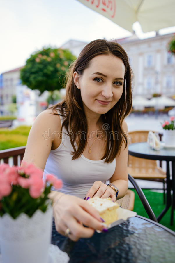 Girl eating fondant cake on table. Girl eating piece of fondant cake on table, outdoor restaurant royalty free stock images
