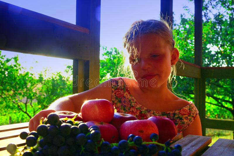 Girl is eating fruits. Apples and grapes on a table. The little girl is sitting at a table on a verandah and eati stock photos