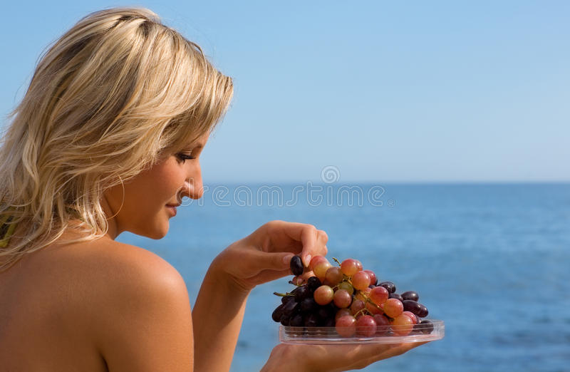 Girl eating grapes at the beach by the sea. Attractive girl eating grapes at the beach by the sea royalty free stock images