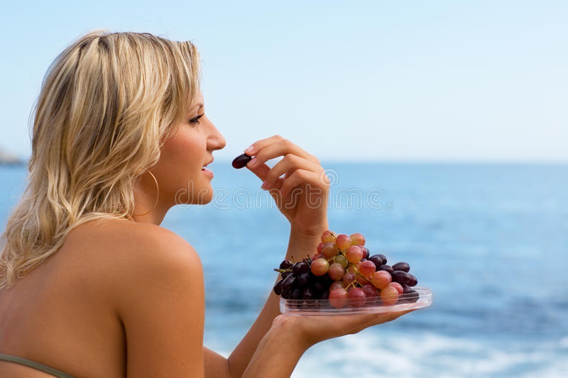 Girl eating grapes at the beach by the sea. Attractive girl eating grapes at the beach by the sea stock images