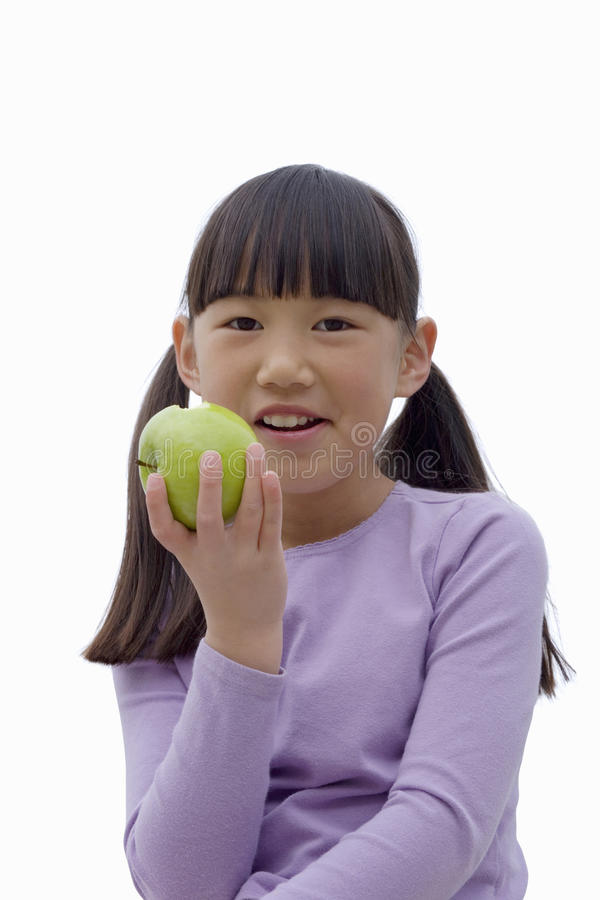 Girl eating green apple, smiling, front view, close-up, portrait, cut out stock photography