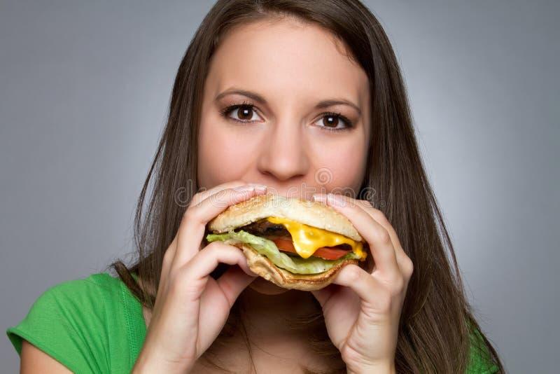 Girl Eating Hamburger. Beautiful girl eating hamburger food royalty free stock images