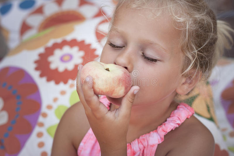 Girl eating a healthy fruit snack stock images