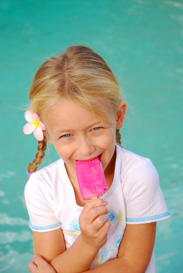 Girl eating ice-cream. A cute little caucasian white girl with happy smiling facial expression holding a pink sorbet ice-cream in her hand and eating it eating royalty free stock photos