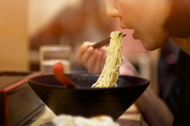 A girl eating Japanese noodles in Japanese restaurant. Asian, food, meal, chinese, young, happy, healthy, female, lunch, person, bowl, cuisine, beautiful royalty free stock image