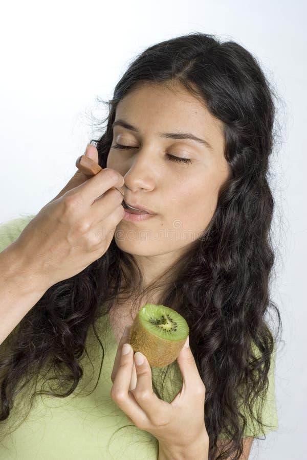 Girl eating kiwi royalty free stock photography