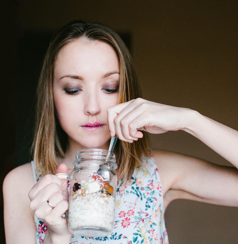 Girl eating muesli out of Cup stock images