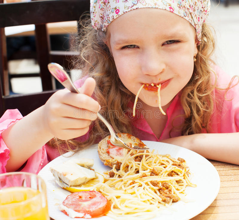 Girl eating pasta. Child eating pasta at cafe royalty free stock photography