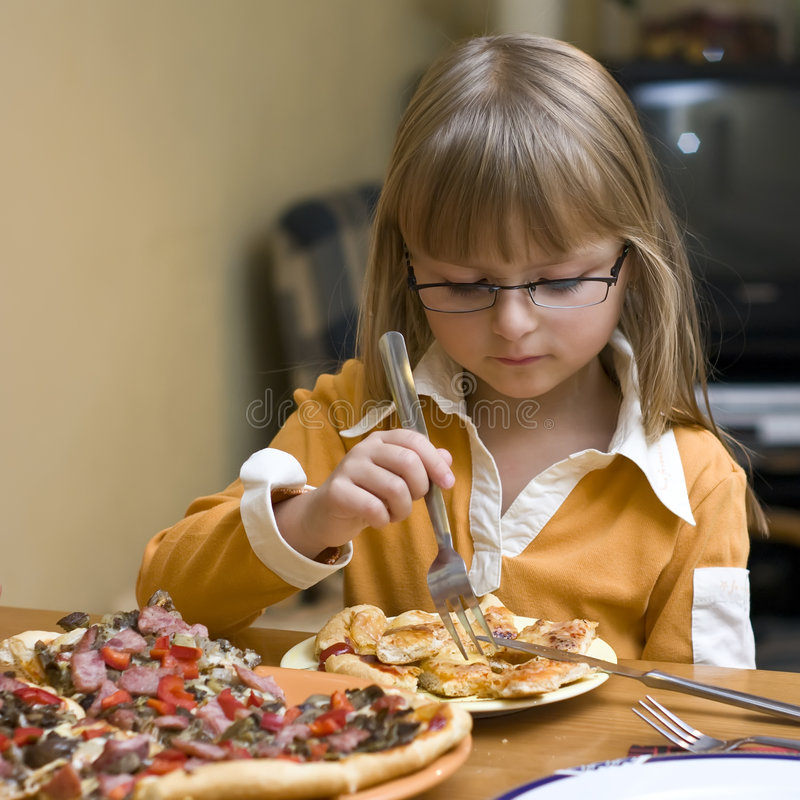 Girl eating pizza. A cute girl eating homemade pizza, struggling with fork and knife. She's blond and wearing eyeglasses stock photos