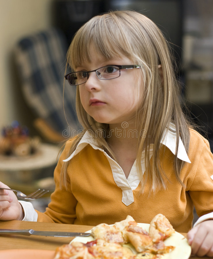 Girl eating pizza. A cute girl eating homemade pizza, struggling with fork and knife. She's blond and wearing eyeglasses royalty free stock image