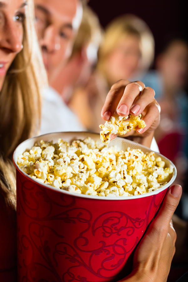 Girl eating popcorn in cinema or movie theater. Woman eating large container of popcorn in cinema or movie theater stock image
