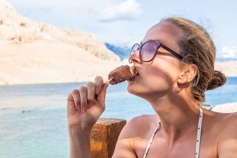 Girl eating popsicle ice pop in shade on picture perfect beach in summer. royalty free stock images