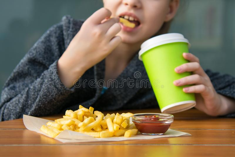 Girl eating potatoes with sauce and drinking a soda while sitting at the table royalty free stock photo
