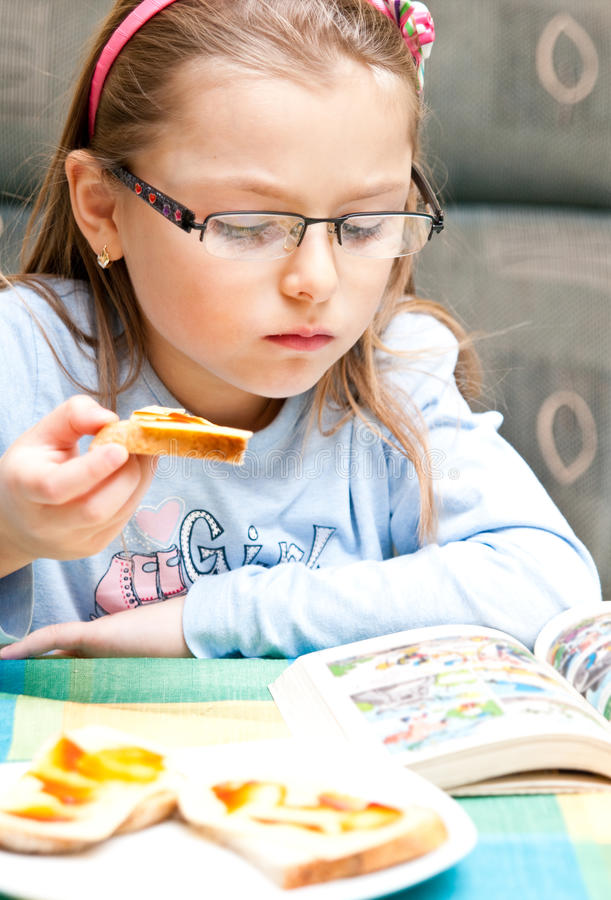 Girl eating and reading. Portrait of young girl eating sandwich and reading book royalty free stock photography