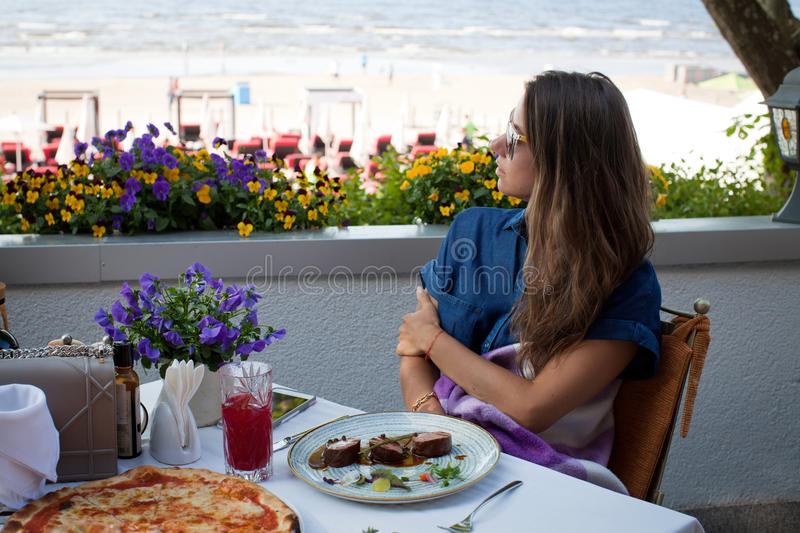 Girl eating in restaurant on the beach. Summer holidays and vacation - girl eating in restaurant on the beach royalty free stock images