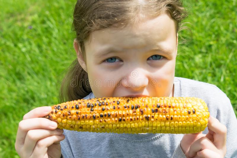 Girl eating a roasted corn cob, closeup view royalty free stock images